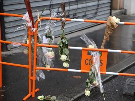 Des fleurs sont disposées en mémoire des victimes sur les barrières délimitant la zone de l'incendie -LyonMag