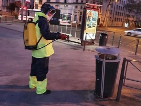 Un agent désinfecte une poubelle - DR