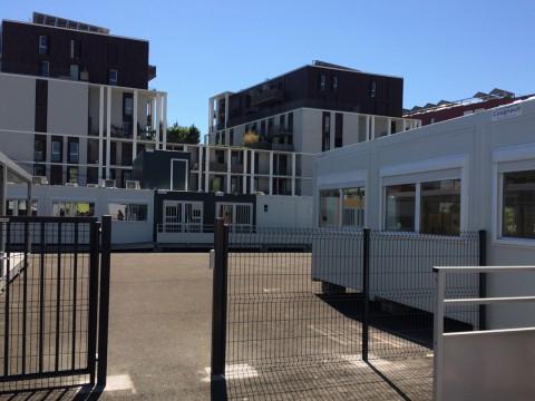 La cour, des préfabriqués et en arrière-plan le quartier de la Zac du Bon Lait - LyonMag